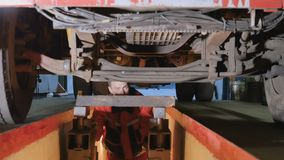Mechanic under bottom of truck. Auto mechanic is under the bottom of truck. Professional worker checks the parts of truck from the down. Man views left and right stock footage