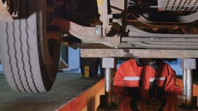 Mechanic under bottom of truck checks the wheel. Auto mechanic is under the bottom of truck. Professional worker checks the parts of truck from the down. Man stock footage