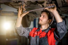 Mechanic under car in garage examing tire and technical condition. Auto mechanic working at auto repair shop under car with tool stock images