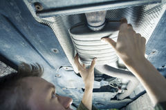 Mechanic under car. Male mechanic replacing exhaust pipe under car Royalty Free Stock Images