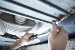 Mechanic under car. Mechanic tightening with ratchet under car platform stock photo
