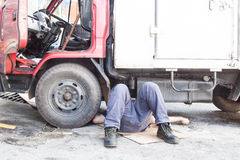 Mechanic under truck reparing dirty greasy oily engine with prob Royalty Free Stock Photos