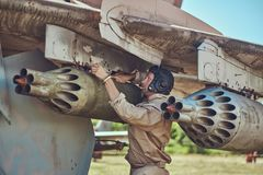 Mechanic in uniform and flying helmet repair old war fighter-interceptor in an open-air museum. Stock Photography
