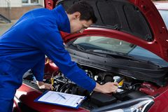 Mechanic in uniform repairing car Royalty Free Stock Photos
