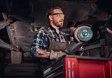 Mechanic in a uniform and safety glasses holds an angle grinder while standing under lifting car in a repair garage. Auto mechanic in a uniform and safety Royalty Free Stock Image