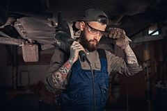 Mechanic in a uniform and safety glasses holds an angle grinder while standing under lifting car in a repair garage. Auto mechanic in a uniform and safety Royalty Free Stock Photography