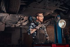 Mechanic in a uniform and safety glasses holds an angle grinder while standing under lifting car in a repair garage. Auto mechanic in a uniform and safety Royalty Free Stock Photos