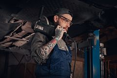 Mechanic in a uniform and safety glasses holds an angle grinder while standing under lifting car in a repair garage. Auto mechanic in a uniform and safety Stock Photos