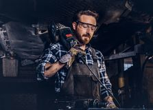 Mechanic in a uniform and safety glasses holds an angle grinder while standing under lifting car in a repair garage. Auto mechanic in a uniform and safety Royalty Free Stock Photo