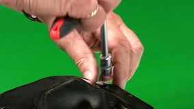 Mechanic unscrewing gearbox cover. Close up of hands of  a mechanic disassembling car gearbox by unscrewing bolts. Isolated on green background stock video