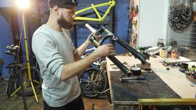 The mechanic unscrews the metal pin assembles a bike in his workshop. A man bike mechanic with a beard assembles a mountain bike in his workshop. A man wearing stock video footage