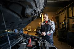 Mechanic using booster cables to start-up a car engine. Mechanic using booster cables to start-up a car stock image