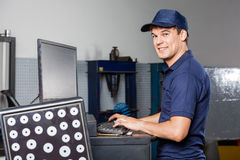 Mechanic Using Computer In Auto Repair Shop. Side view portrait of male mechanic using computer in auto repair shop royalty free stock photos