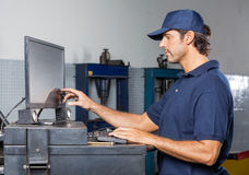 Mechanic Using Computer In Repair Shop. Side view of male mechanic using computer in auto repair shop Stock Photos
