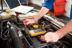 Mechanic using diagnostic tool on engine. At the repair garage royalty free stock photo