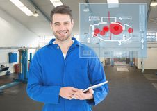 Mechanic using digital tablet against car mechanics interface in background Stock Photos