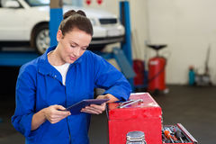 Mechanic using her tablet pc Stock Photography