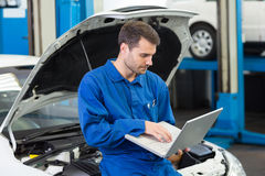 Mechanic using his laptop Royalty Free Stock Photos