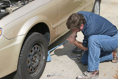 Mechanic Using Jack. A mechanic using a jack to lift a car and remove the tire stock photo