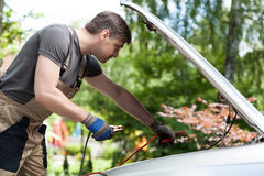 Mechanic using jumper cables to start a car battery. Horizontal Stock Photos