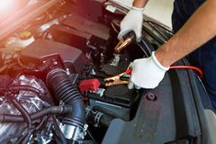 Mechanic using jumper cables to start a car Royalty Free Stock Photos