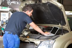 Mechanic using laptop. While repairing car in garage royalty free stock photography