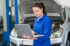 Mechanic using laptop on car Royalty Free Stock Photos