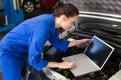 Mechanic using laptop on car Stock Photos