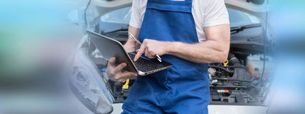 Mechanic using laptop for checking car engine Royalty Free Stock Image