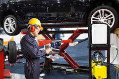 Mechanic using laptop computer for maintenance modern car Stock Photos