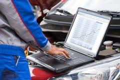 Mechanic Using Laptop For Examining Car Engine. Close-up Of Male Mechanic Using Laptop For Examining Car Engine Stock Image