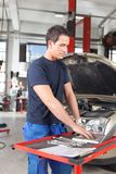 Mechanic using laptop in garage Royalty Free Stock Images
