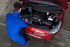 Mechanic using laptop while repairing car stock images