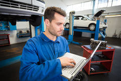 Mechanic using a laptop to work Stock Image
