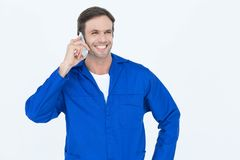 Mechanic using mobile phone over white background Royalty Free Stock Photo