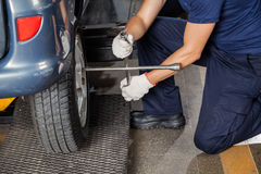 Mechanic Using Rim Wrench To Fix Tire Royalty Free Stock Image