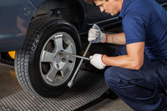 Mechanic Using Rim Wrench To Tighten Car Tire. Side view of male mechanic using rim wrench to tighten car tire at garage Royalty Free Stock Images