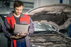 Mechanic Examining Car Engine With Help Of Laptop. Mechanic using special laptop computer to check car engine stock photos