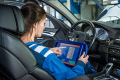 Mechanic Using Tablet Computer In Car At Garage stock photo