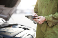 Mechanic using tablet computer Stock Photography