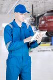 Mechanic using tablet computer in workshop. Young mechanic using a digital tablet computer while standing in the workshop Stock Photo