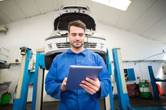 Mechanic using a tablet pc Royalty Free Stock Photos