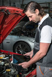 Mechanic using a tablet pc at the repair garage Stock Image