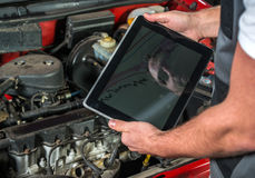 Mechanic using a tablet pc at the repair garage Royalty Free Stock Images
