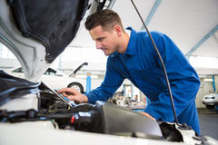 Mechanic using tablet to fix car. At the repair garage royalty free stock photo