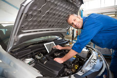 Mechanic using tablet to fix car Stock Photography