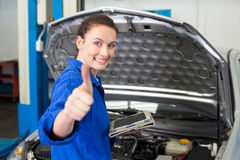 Mechanic using tablet to fix car Royalty Free Stock Photos