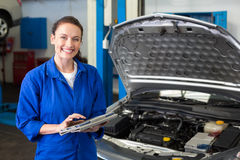 Mechanic using tablet to fix car Royalty Free Stock Images