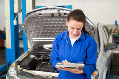 Mechanic using tablet to fix car Stock Images