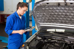 Mechanic using tablet to fix car Stock Image